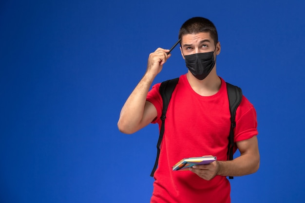 Männlicher student der vorderansicht im roten t-shirt, das rucksack in der schwarzen sterilen maske hält, die das heft und das stiftdenken auf dem blauen hintergrund hält.