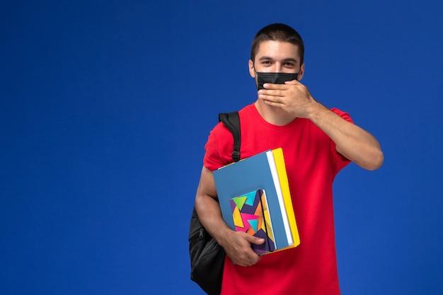 Männlicher student der vorderansicht im roten t-shirt, das rucksack in der schwarzen sterilen maske hält, die heft und dateien auf dem blauen hintergrund hält.