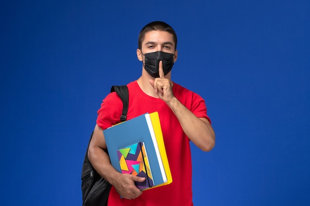 Männlicher student der vorderansicht im roten t-shirt, das rucksack in der schwarzen sterilen maske hält, die hefte auf dem blauen schreibtisch hält.