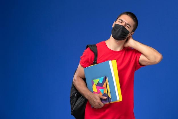 Männlicher student der vorderansicht im roten t-shirt, das rucksack in der schwarzen sterilen maske trägt, die hefte hält, die nackenschmerzen auf blauem hintergrund haben.
