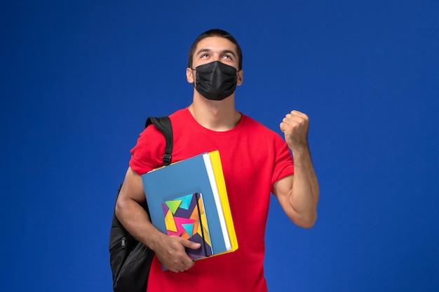 Männlicher student der vorderansicht im roten t-shirt, das rucksack in schwarzer steriler maske trägt, die heft und dateien auf blauem schreibtisch hält.
