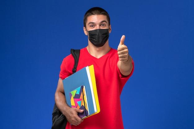 Männlicher student der vorderansicht im roten t-shirt, das rucksack in schwarzer steriler maske trägt, die hefte auf dem blauen hintergrund hält.
