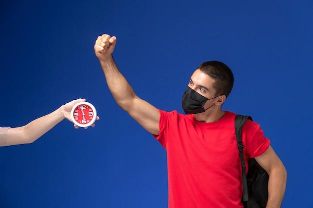 Männlicher student der vorderansicht im roten t-shirt, das rucksack mit maske trägt, die auf blauem hintergrund aufwirft.