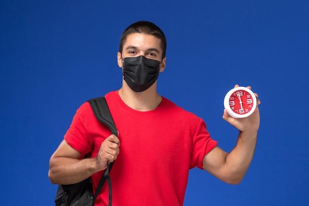 Männlicher student der vorderansicht im roten t-shirt, der rucksack mit maske hält uhren auf dem blauen hintergrund trägt.
