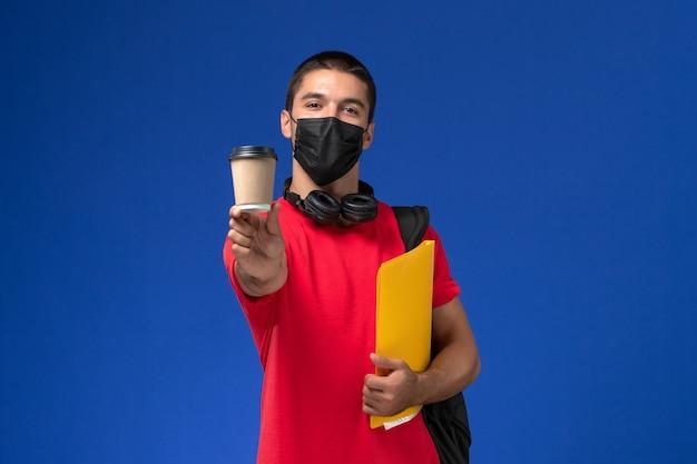 Männlicher student der vorderansicht in der roten t-shirt tragenden maske mit dem rucksack, der gelbe datei und kaffee auf dem blauen hintergrund hält.