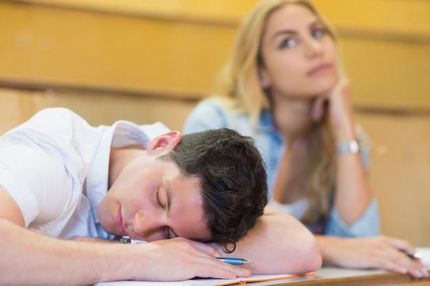 Männlicher student, der während des unterrichts an der universität einschläft