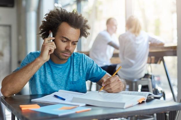 Männlicher student mit afrikanischer frisur, der am hölzernen schreibtisch sitzt und mit seinem besten freund am smartphone spricht, die neuesten nachrichten bespricht und ernsthaft im lehrbuch schaut, unterstreicht etwas mit bleistift