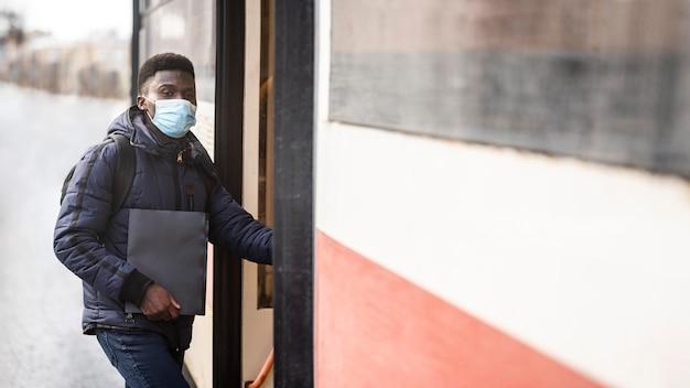 Männlicher student mit maske, die bücher an straßenbahnhaltestelle hält
