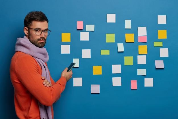 Männlicher student überprüft arbeitsplan, benutzt modernes smartphone, steht im profil, trägt brille, schal und pullover
