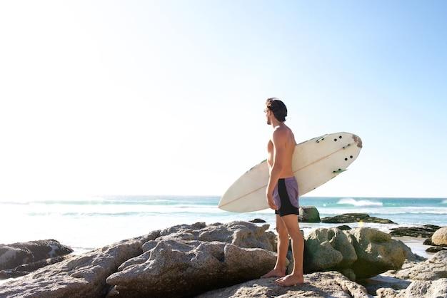 Männlicher surfer, der das meer betrachtet