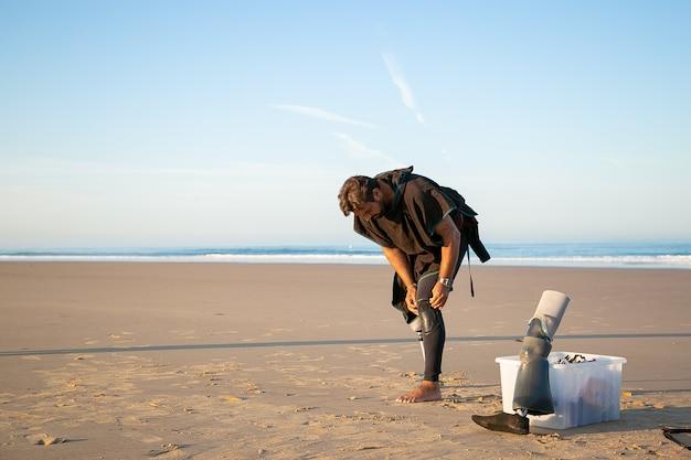 Männlicher surfer, der künstliches glied trägt und neoprenanzug am ozeanstrand anzieht