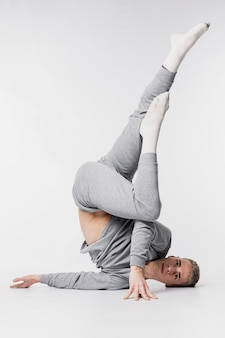 Männlicher tänzer in den socken und in trainingsanzug, die mit den beinen oben aufwerfen