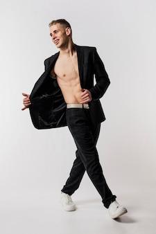 Männlicher tänzer in der klage und in turnschuhen, die mit blazer lächeln und aufwerfen, öffneten sich