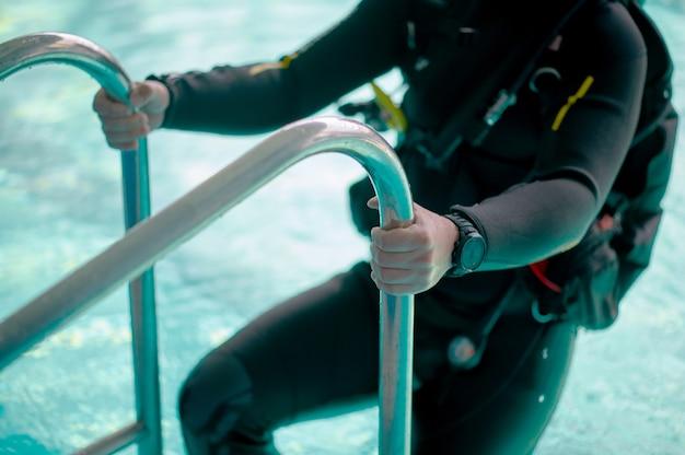 Männlicher taucher in tauchausrüstung klettert aus dem pool