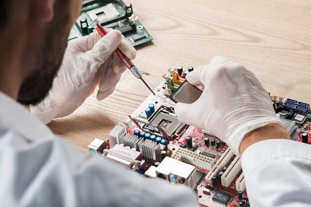 Männlicher techniker, der an computermotherboard arbeitet