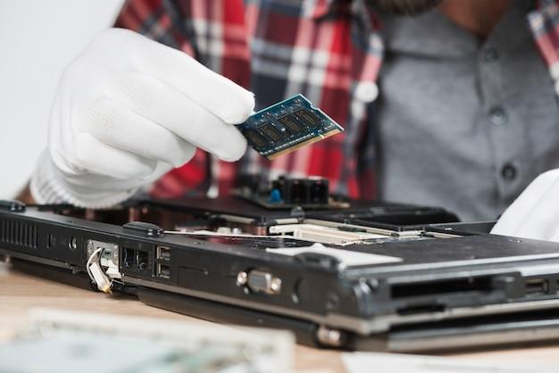 Männlicher techniker, der chip des computers hält