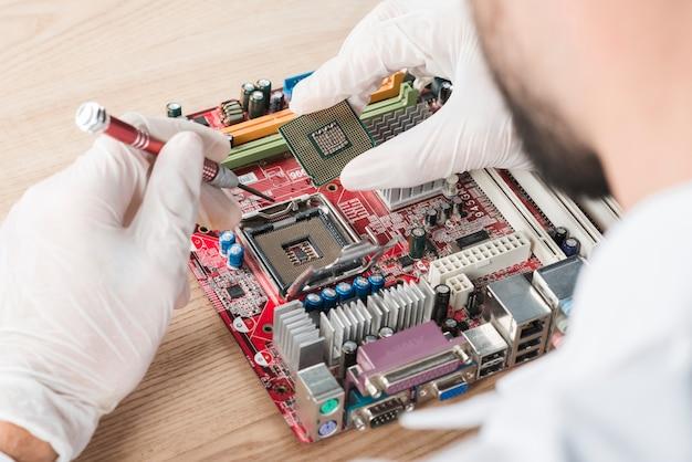 Männlicher techniker, der chip in computermotherboard auf hölzernem schreibtisch einfügt