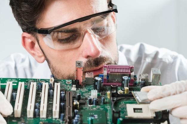 Männlicher techniker, der chip in computermotherboard einfügt