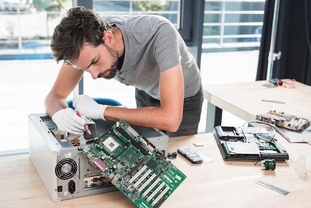 Männlicher techniker, der computer in der werkstatt repariert