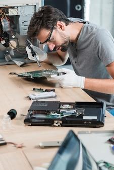 Männlicher techniker, der computermotherboard auf hölzernem schreibtisch repariert