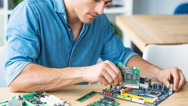 Männlicher techniker, der die hardwareausrüstung zusammenbaut