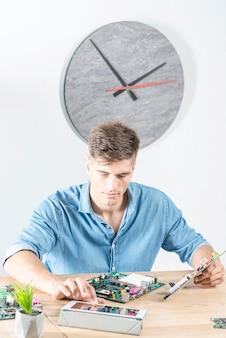 Männlicher techniker, der digitale tablette beim reparieren des motherboards verwendet