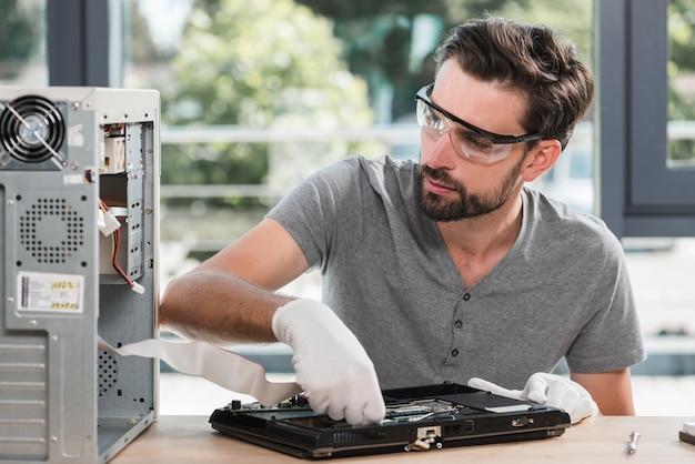 Männlicher techniker, der gebrochenen laptop in der werkstatt überprüft