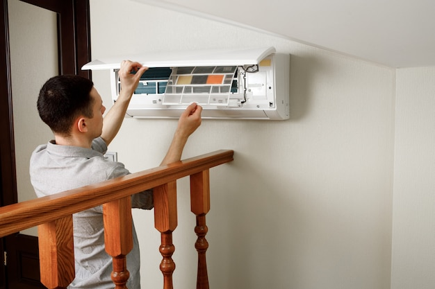 Männlicher techniker, der klimaanlage drinnen reinigt