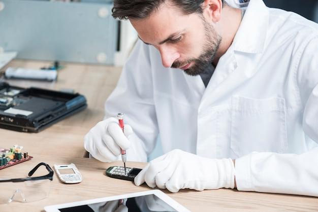 Männlicher techniker, der mobiltelefon repariert