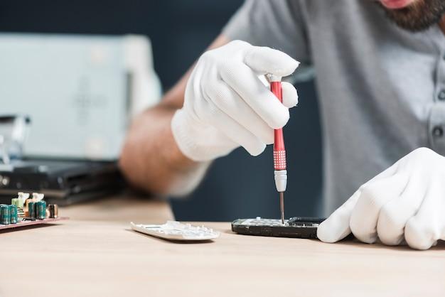 Männlicher techniker, der mobiltelefon über hölzernem schreibtisch repariert