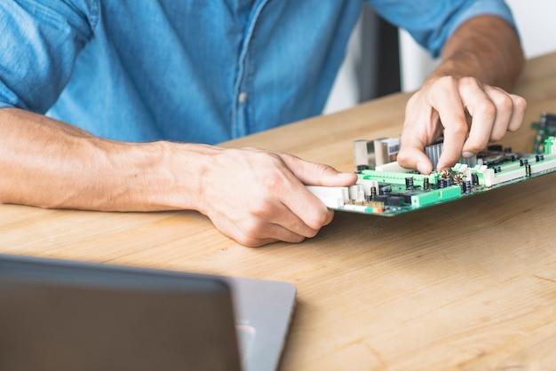 Männlicher techniker, der motherboard am werktisch repariert