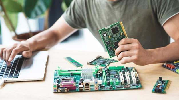 Männlicher techniker, der motherboard unter verwendung des laptops repariert