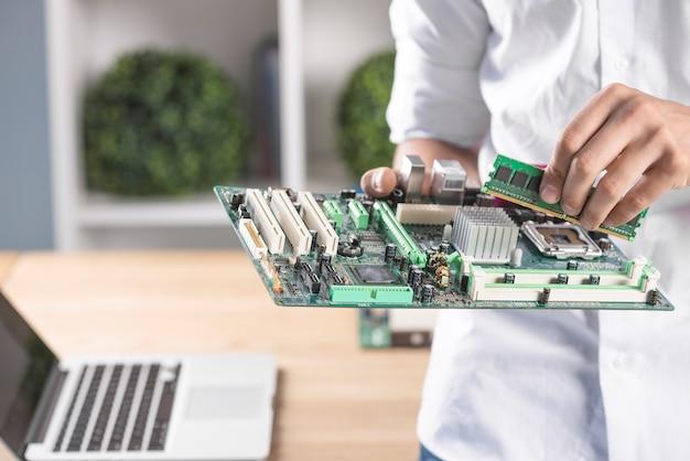 Männlicher techniker, der ram in modernes pc-computermotherboard einfügt