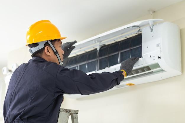 Männlicher techniker, der zuhause klimaanlagensicherheitsuniform repariert.