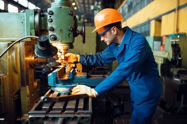 Männlicher techniker in uniform und helm arbeitet an drehmaschine, anlage. industrielle produktion, metalltechnik, herstellung von kraftmaschinen
