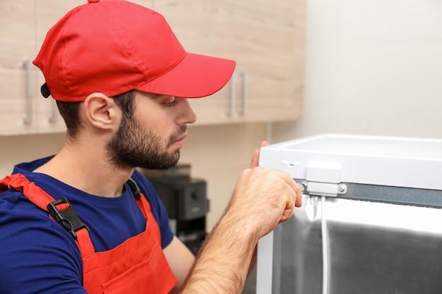Männlicher techniker repariert kühlschrank drinnen