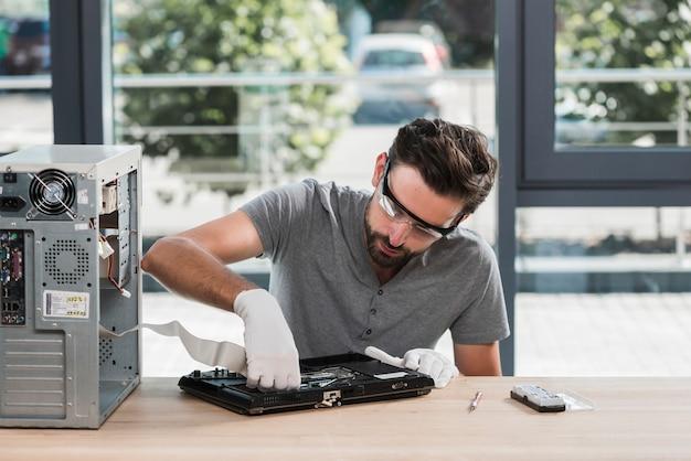 Männlicher technikerfestlegungscomputer in der werkstatt