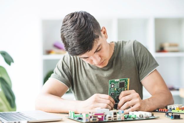 Männlicher technikstudent, der das hardware-teil zusammenbaut