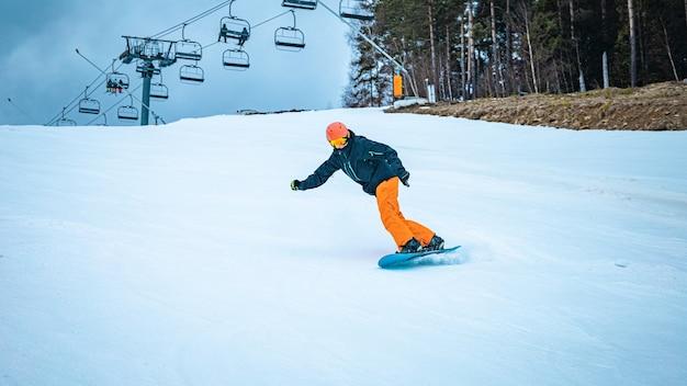 Männlicher teenager, der an einem wolkigen tag mit seinem snowboard eine wendung nimmt
