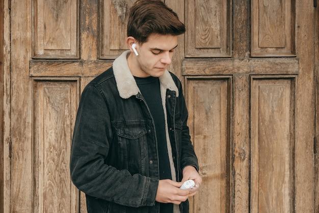Männlicher teenager, der musik mit kabellosen kopfhörern hört