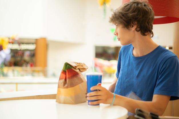 Männlicher teenager mit einem fastfood-paket, das am tisch sitzt und auf eine bestellung wartet