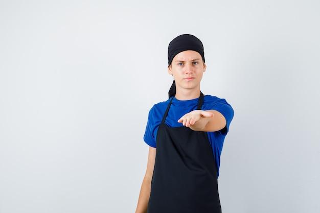 Männlicher teenagerkoch, der die hand vorne im t-shirt, in der schürze ausdehnt und aufrichtig schaut. vorderansicht.