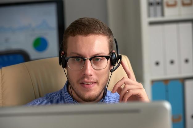 Männlicher telefonist, der in call-center mit kopfhörer arbeitet