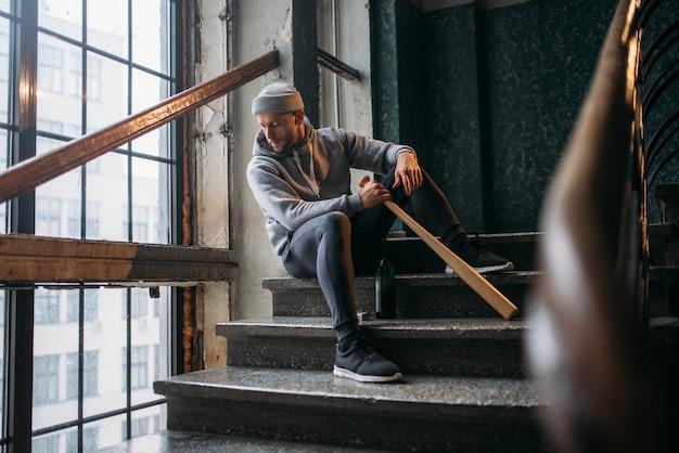 Männlicher theif mit baseballschläger sitzt auf der treppe. straßenräuber wartet auf opfer. verbrechenskonzept, raubangriffsgefahr