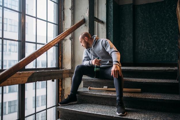 Männlicher theif mit baseballschläger sitzt auf der treppe