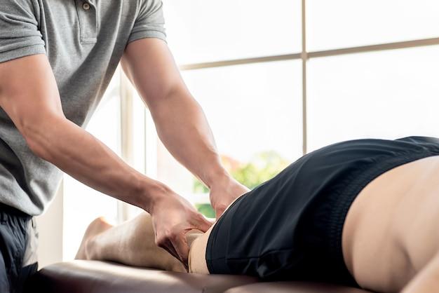 Männlicher therapeut, der dem athletenpatienten auf dem bett in der klinik beinmassage gibt