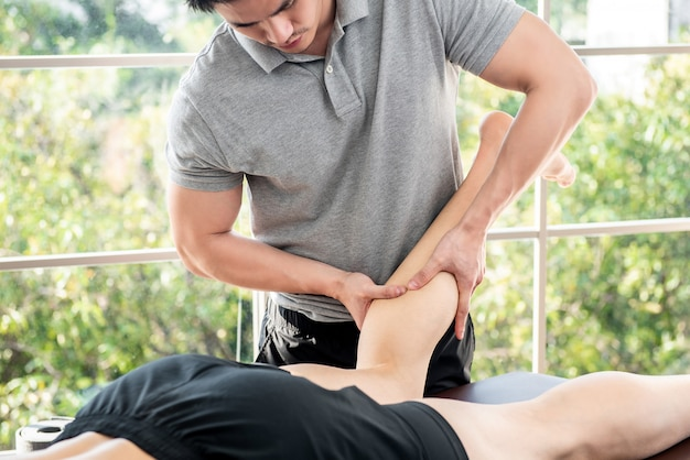 Männlicher therapeut, der dem athletenpatienten in der klinik beinmassage gibt