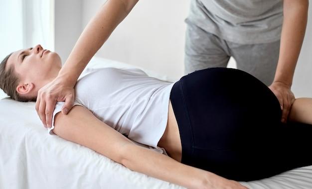 Männlicher therapeut, der sich einer physiotherapie mit einer patientin unterzieht