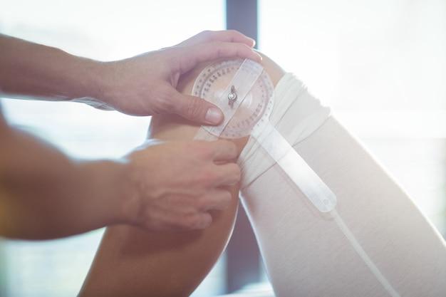 Männlicher therapeut, der weibliches patientenknie mit medizinischem lineal misst