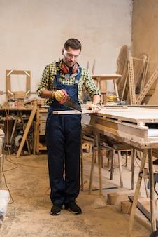 Männlicher tischler, der die hölzerne planke mit handsäge schneidet